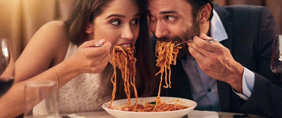 Un couple qui mange des pâtes côte à côte