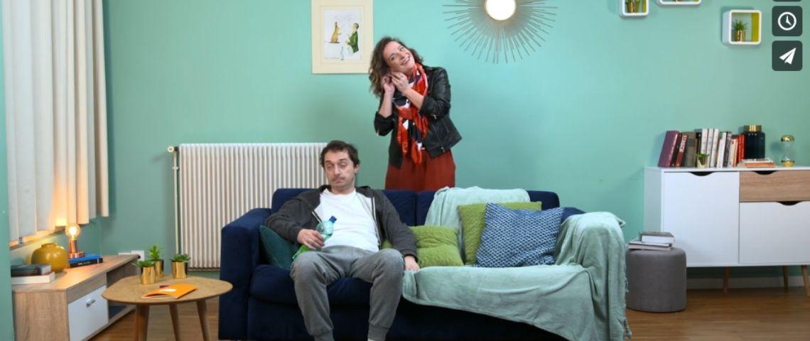 Couple dans un salon, l'homme est assis sur le canapé avec une bouteille de St-Yorre et la femme est débout derrière en train de mettre une boucle d'oreille