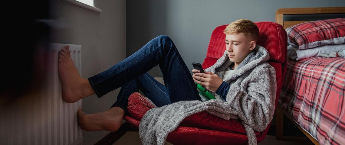 un adolescent, pieds nus dans sa chambre avec un portable dans les mains.