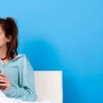 une fille au lit tient son téléphone à la main