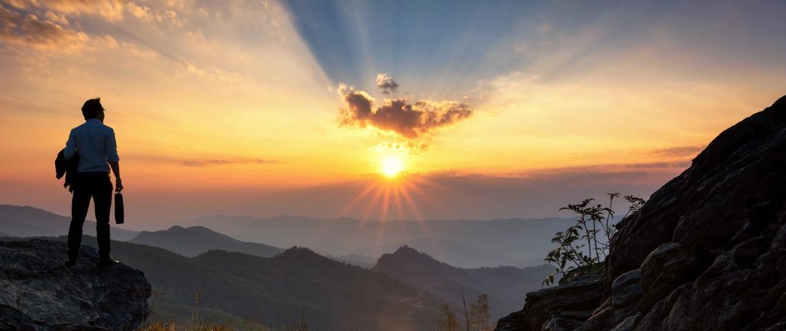 Un homme au sommet d'une montagne en train d'assister au lever du soleil