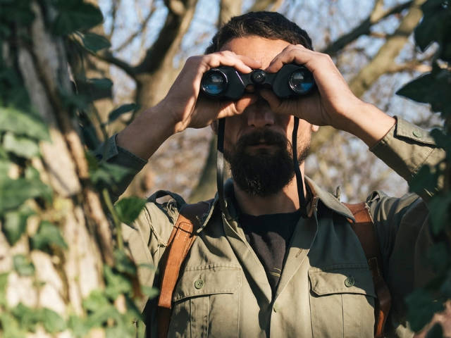Un homme dans la jungle avec des jumelles