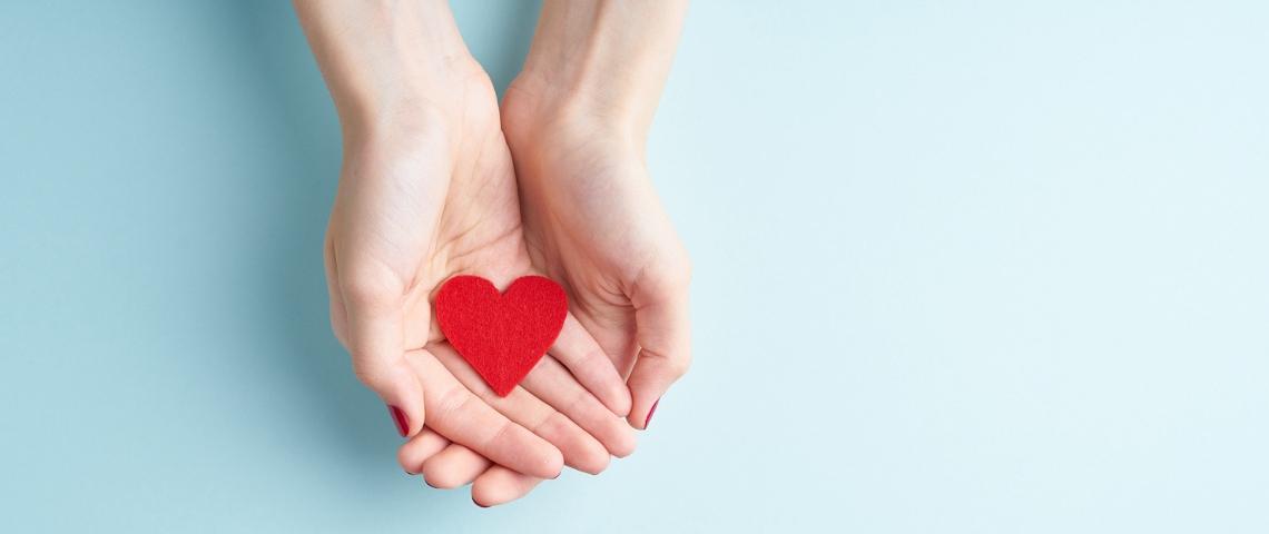 deux mains de femme tenant un coeur en papier rouge