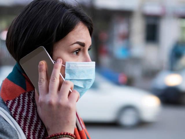 Une femme portant un masque de protection au téléphone