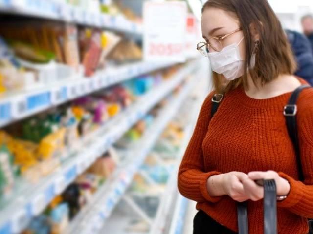 Une masque qui fait ses courses dans un supermarché avec un masque