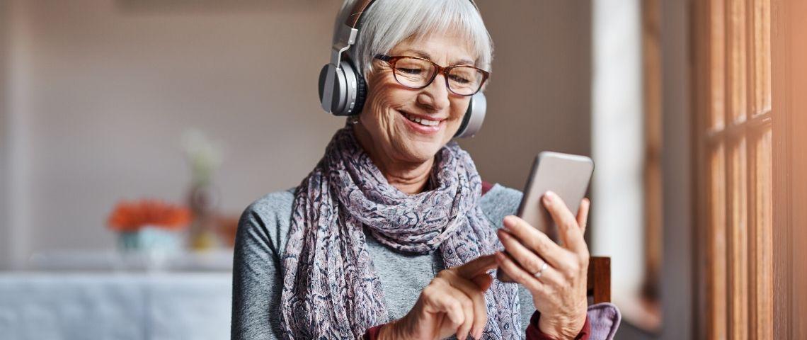 Une femme avec les cheveux blanc qui regarde son smartphone