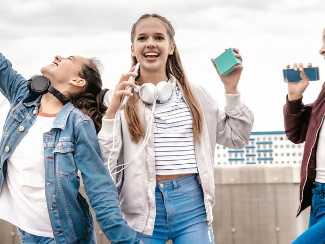 trois adolescentes dansent avec leur portable.