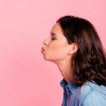 Un homme et une femme qui se font un bisou à distance sur un fond rose