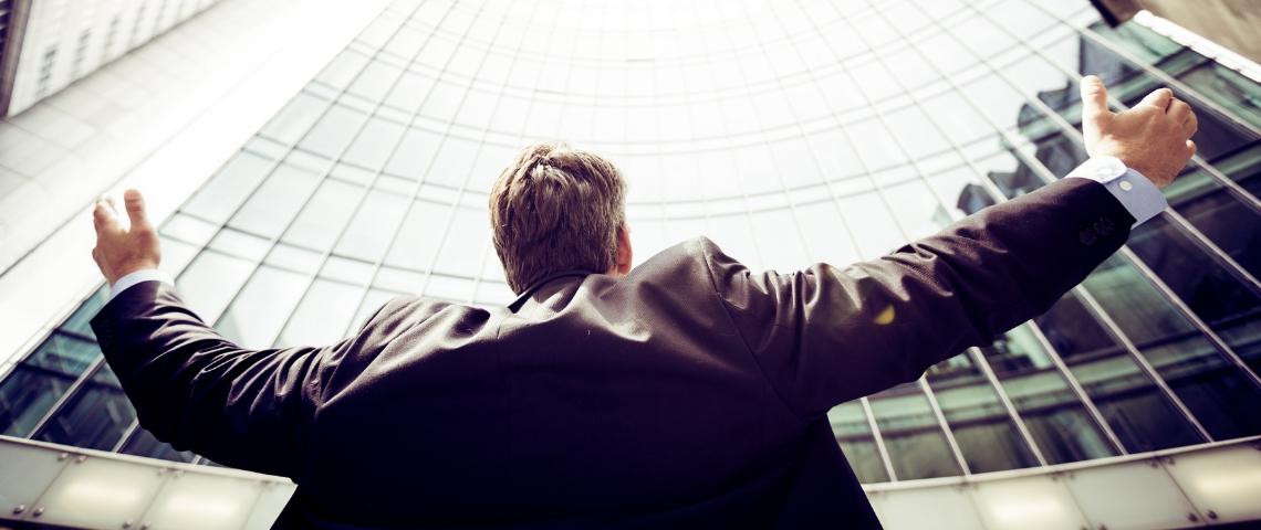 Un homme les bras ouverts devant une tour