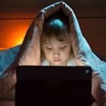 Une petite fille qui joue sur un ordinateur cachée sous sa couette