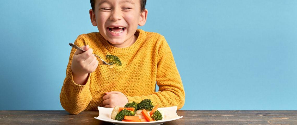 Un enfant qui mange des brocolis