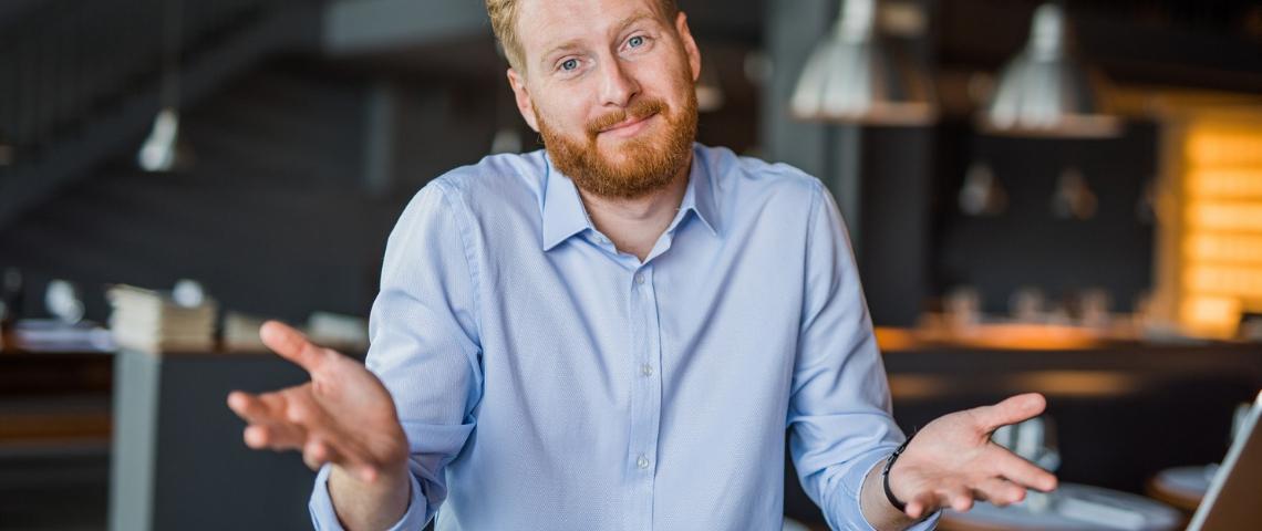 Un homme roux avec une chemise bleue en train de faire un geste d'excuses