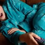 Une femme affalée sur son canapé en pyjama