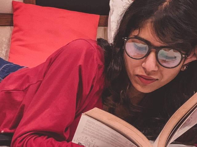 Une femme indienne lisant un livre sur son lit