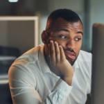 Un homme qui regarde son écran d'ordinateur dépité
