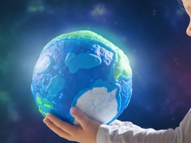 un jeune enfant tenant un globe lumineux entre ses mains