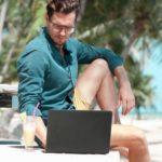 Un homme qui regarde son ordinateur sur la plage
