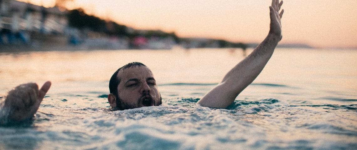 un homme barbu en train de se noyer