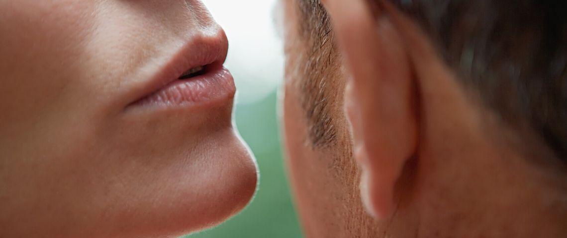 Une femme chuchotte un secret à l'oreille d'un homme
