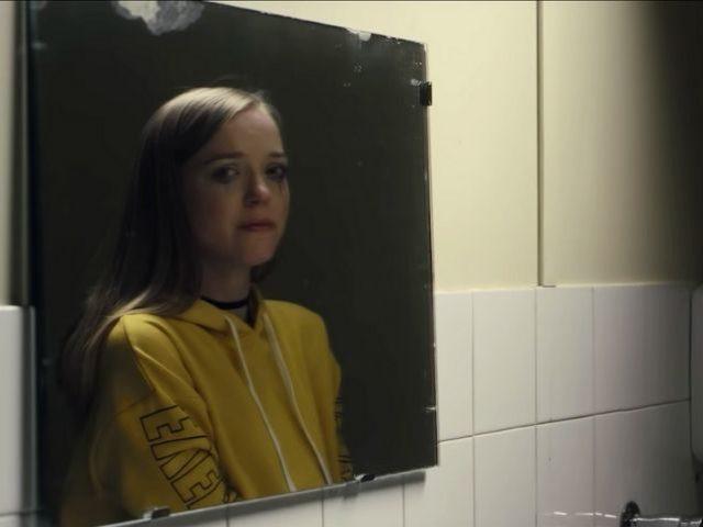 une adolescente pleure devant le miroir