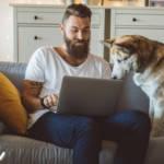Un homme en train de travailler sur son canapé avec son chien