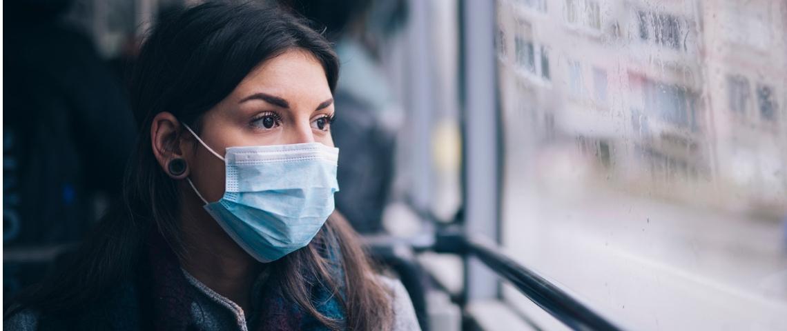 Une femme dans un bus portant un masque chirurgical