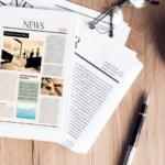 Des journaux posés sur une table avec une tasse de café et des lunettes