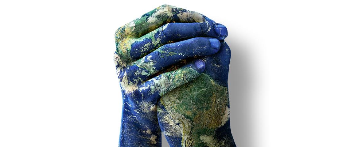 Des mains sur fond de planète Terre