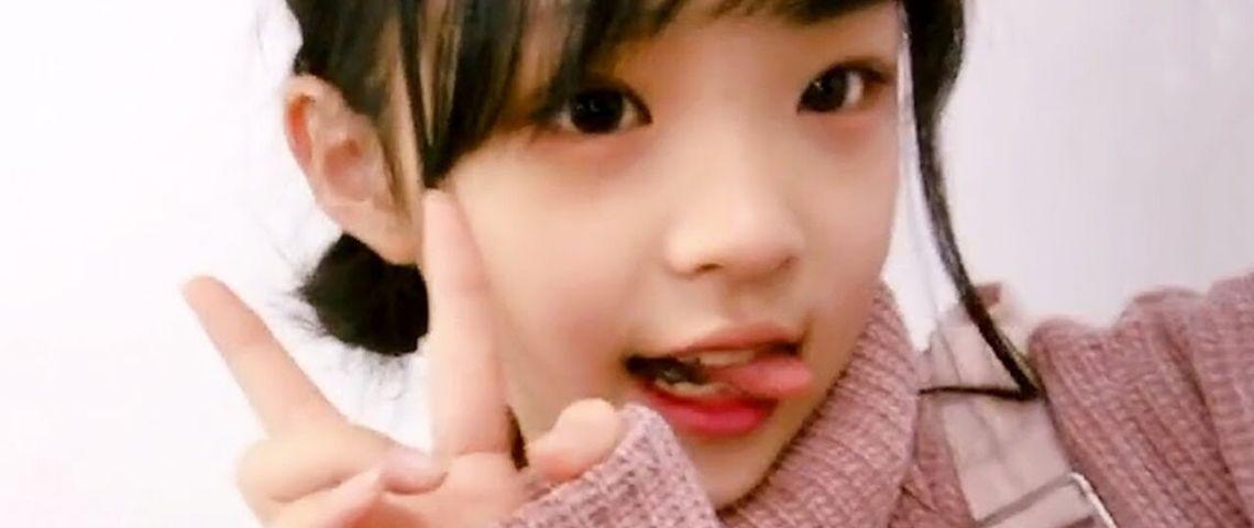 Une petite fille asiatique fait le signe V de victoire