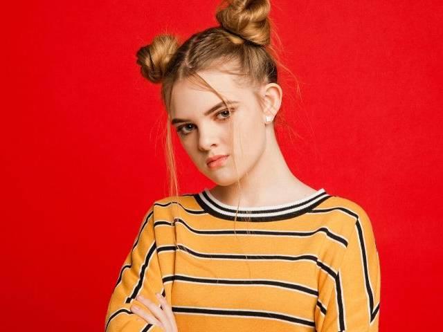 Une adolescente qui fait la tête devant un fond rouge
