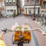 jeune femme en pull jaune sur un vélo à Amsterdam