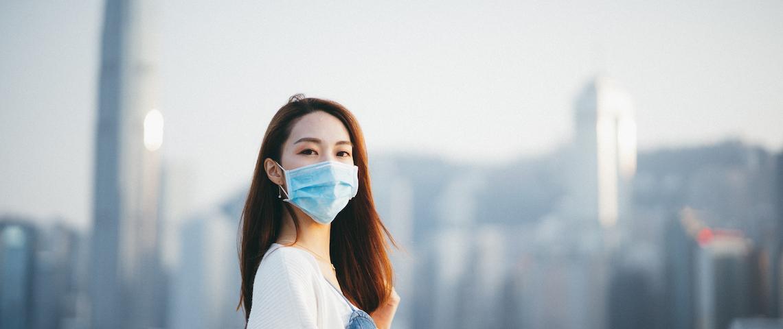 Une jeune femme asiatique, portant un masque de protection, regarde l'objectif sur fond de buildings