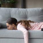 Une femme affalée sur son canapé gris