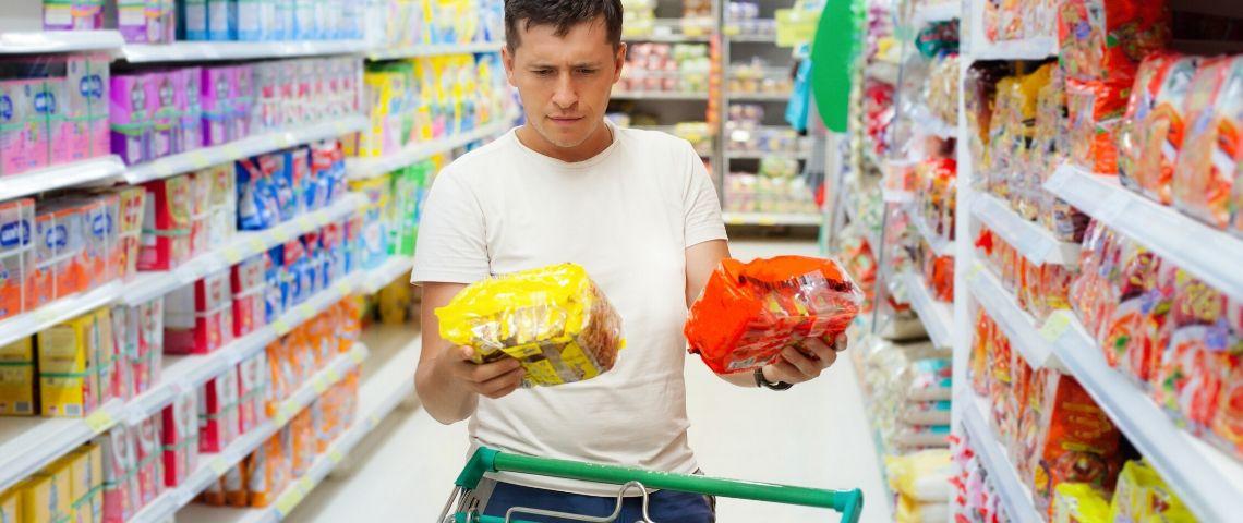 Un homme qui hésite en faisant ses courses au supermarché