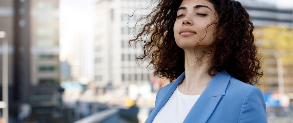 Une femme médite sur la terrasse d'un immeuble