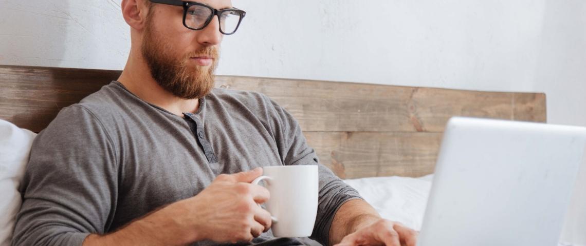 Un homme dans son lit en train de boire un café et d'utiliser son ordinateur