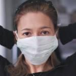 Une femme habillée en noir qui attache un masque chirurgical