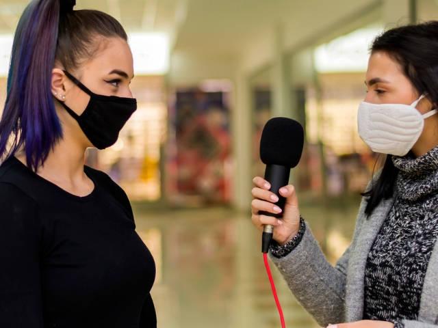Une journaliste en train d'interviewer un femme portant un masque