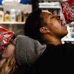 Une femme et un homme qui mangent des chips dans un supermarché