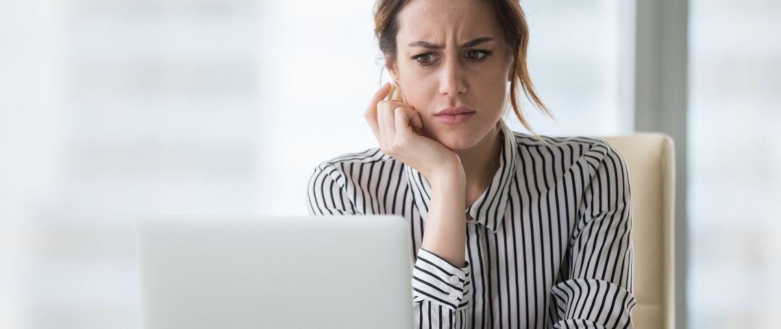 Une femme qui regarde son écran d'ordinateur avec dégoût et surprise