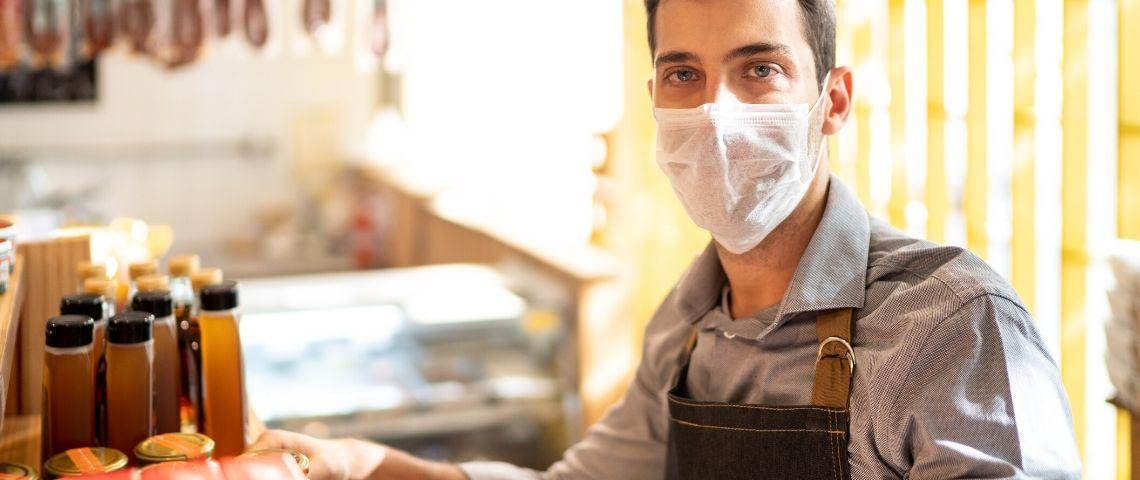 Un homme avec un masque tient un commerce