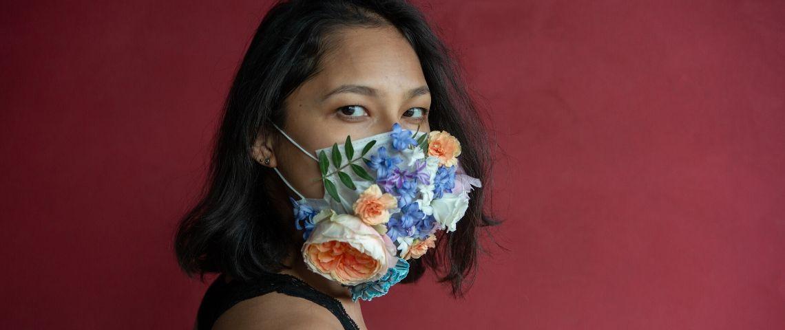 Une femme avec un masque à fleurs sur un fond rouge