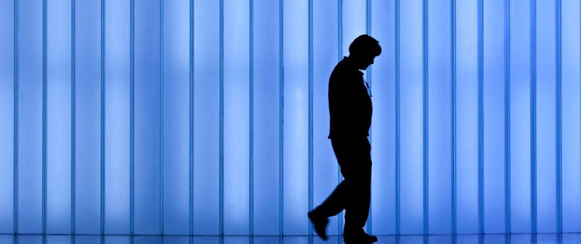 Un homme seul devant un fond bleu
