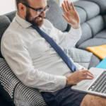 Un homme en caleçon, chemise et cravate en visioconférence dans son salon