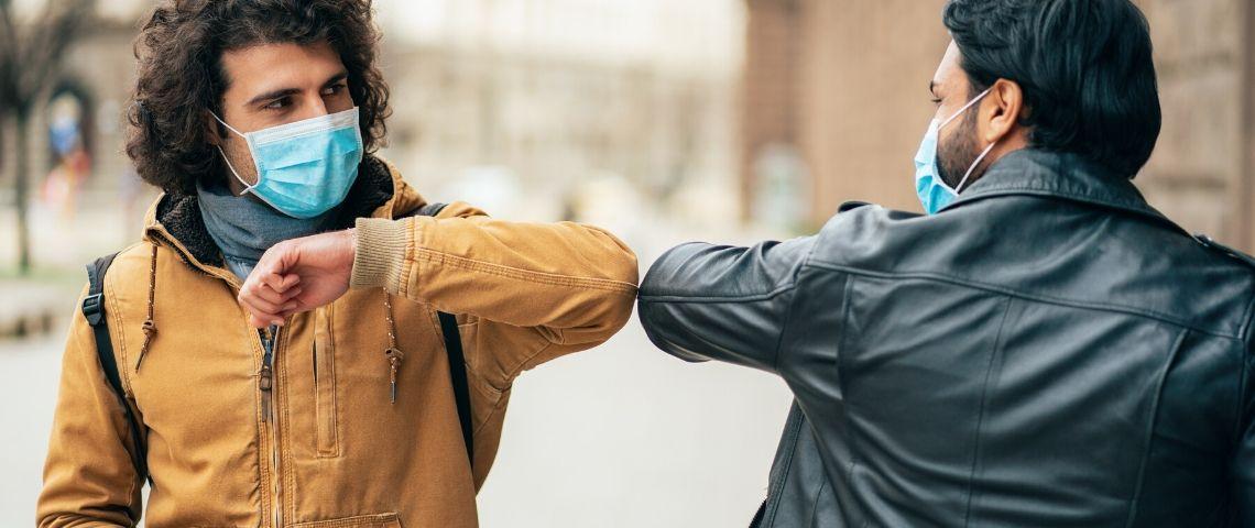 Deux personnes se saluent avec un masque