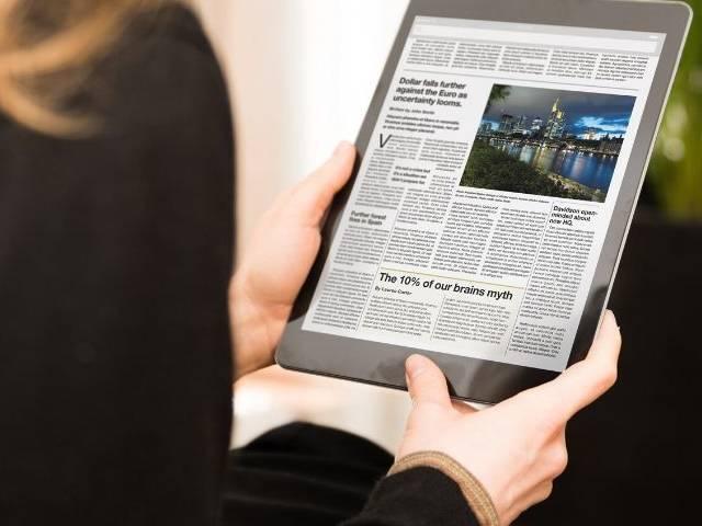 Une femme de dos qui lit le journal sur une tablette