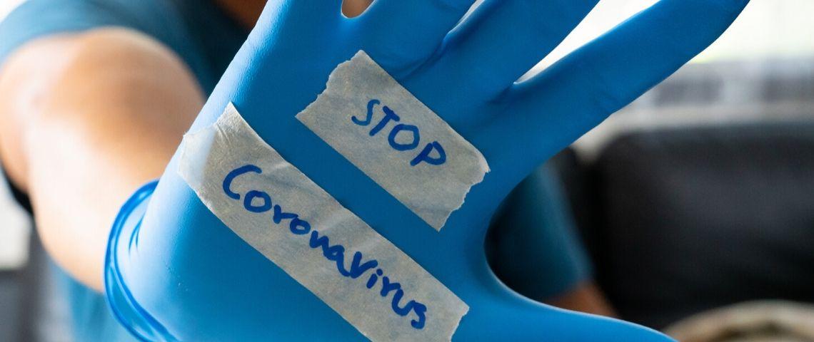 Une main dans un gant en plastique bleu