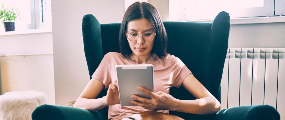 Une femme asiatique tenant une tablette dans un fauteuil vert