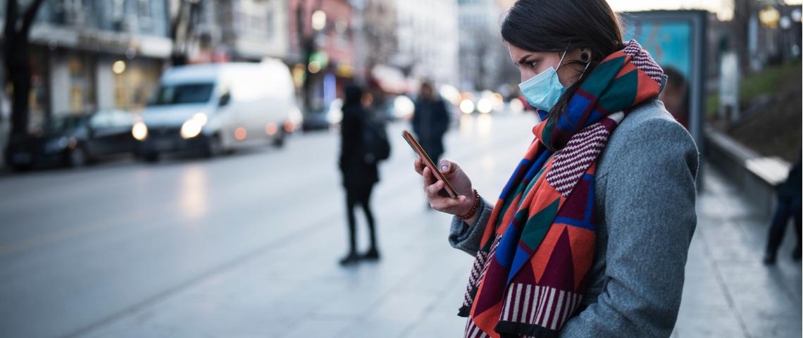 Une femme portant un masque en train d'utiliser son portable