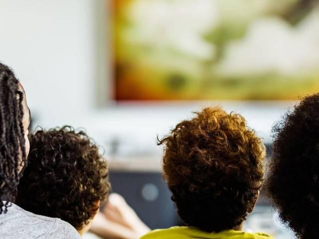 Une famille de 4 personnes de dos en train de regarder la télévision